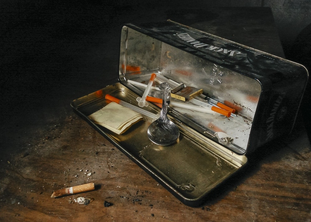 A junky's heroin kit in a Jack Daniels tin at an abandoned house in East Texas
