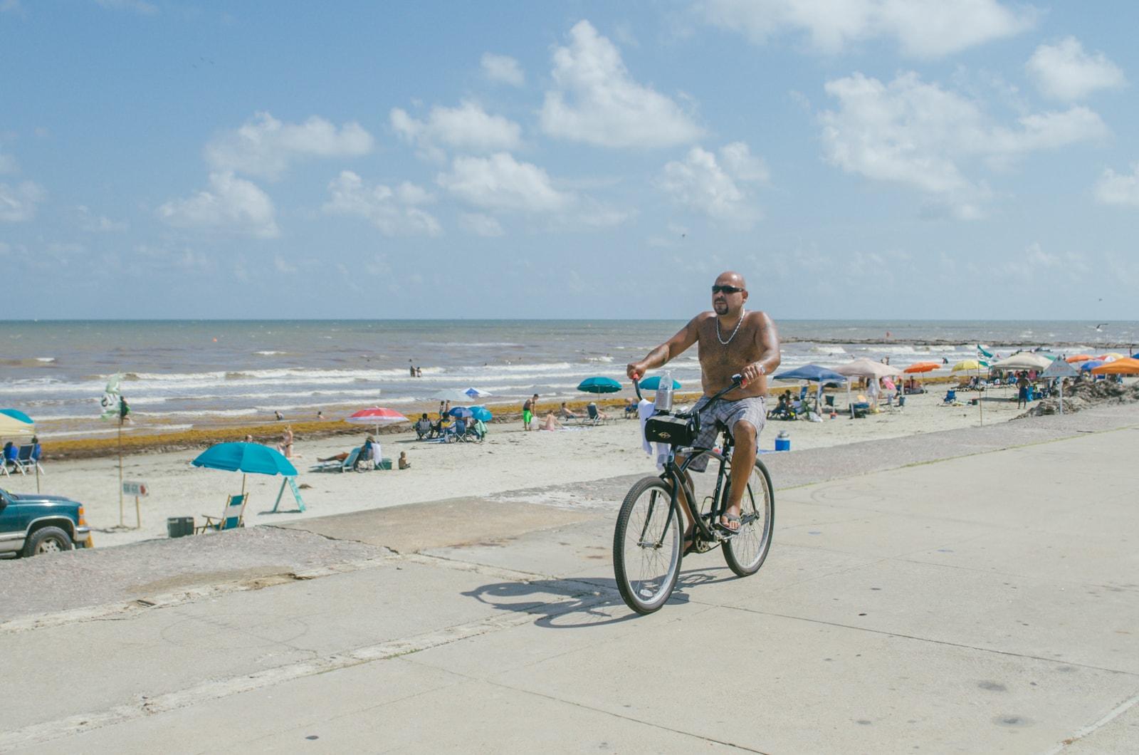 A man riding his bike on the beach
