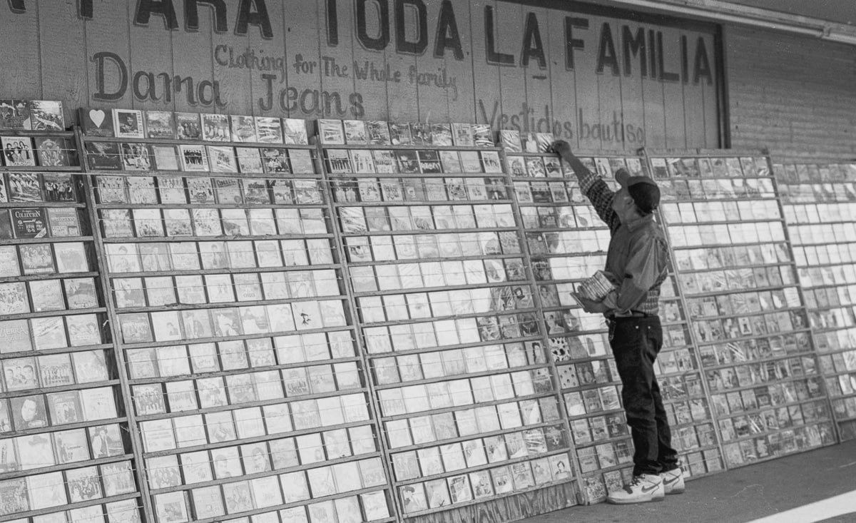 A Hispanic man selling CDs