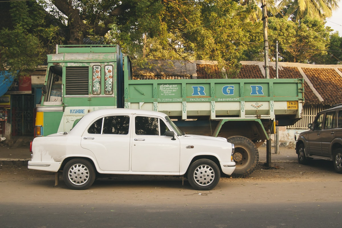 A white Hindustan Ambassador with a Green truck