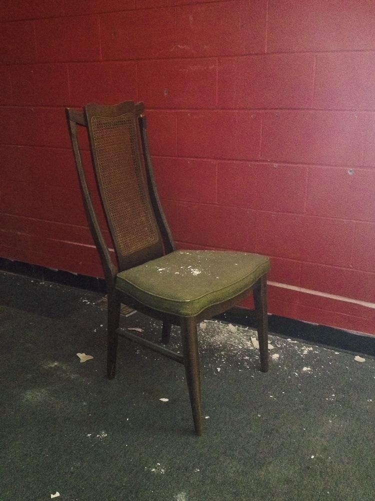An old chair with dry wall on it that fell from the ceiling