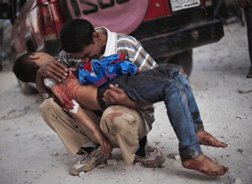 A Syrian man cries while holding the body of his son near Dar El Shifa hospital in Aleppo, Syria, Oct. 3, 2012. The boy was killed by the Syrian army. (Manu Brabo, Associated Press - October 3, 2012)