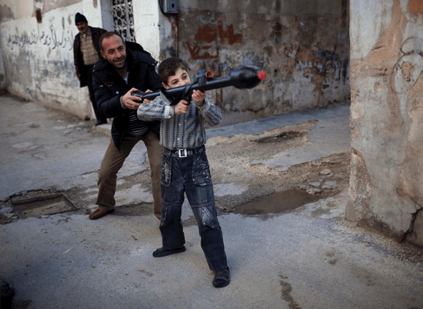 A man teaches Bilal, 11, how to use a toy rocket propelled grenade in Idlib, northern Syria, March 4, 2012. (Rodrigo Abd, Associated Press - March 4, 2012)