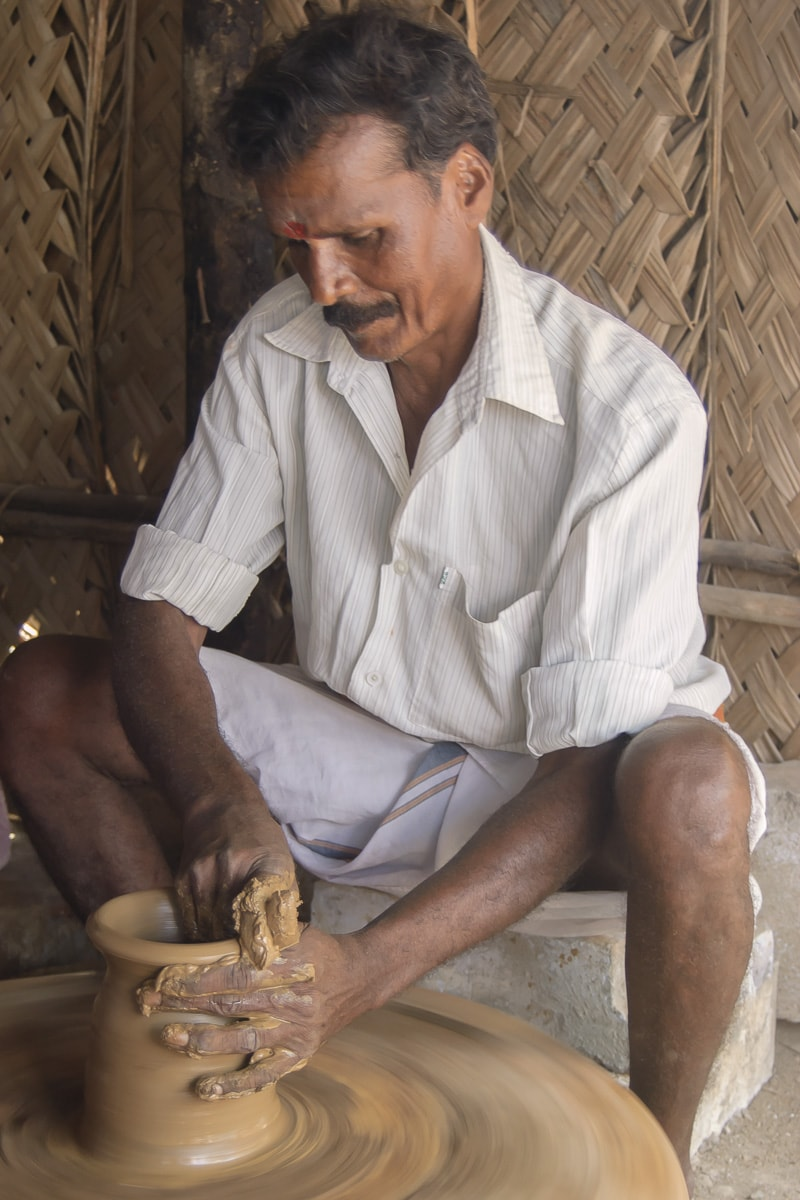 A man making a jar out of clay