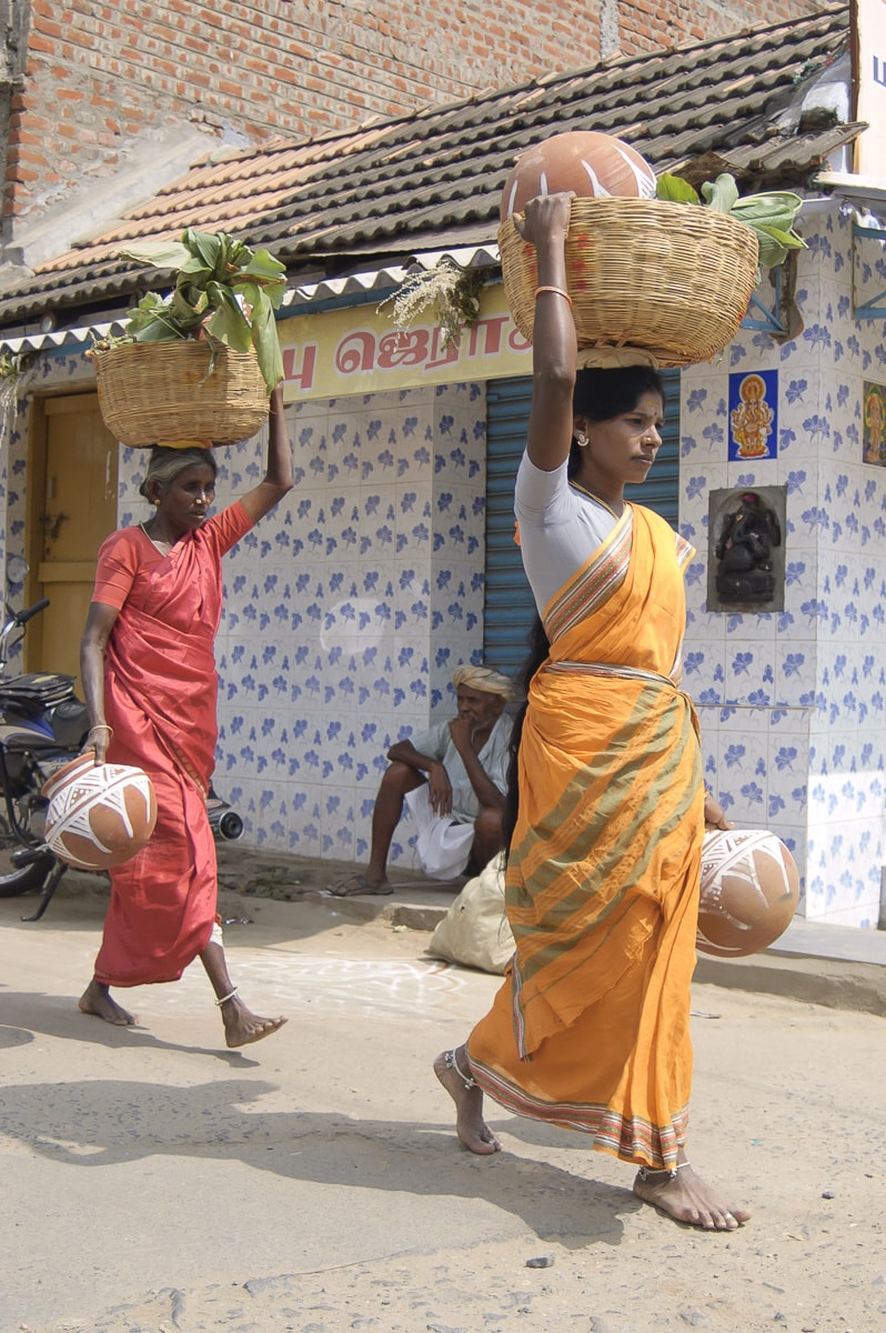 two women carrying baskets on their heads
