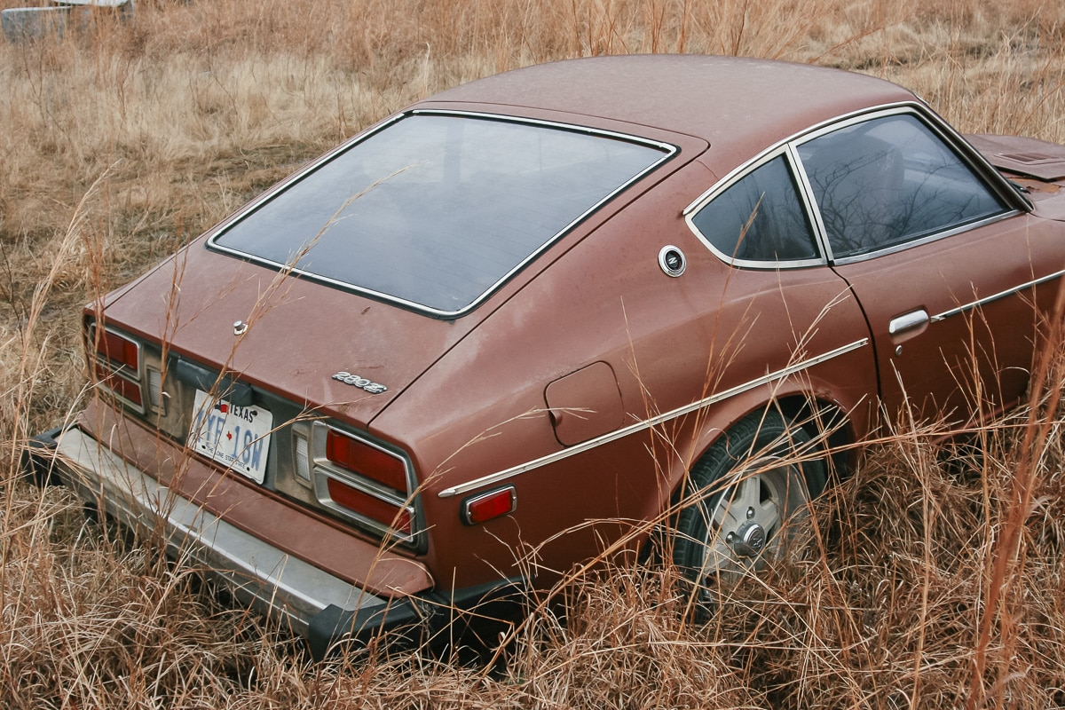 A Datsun 280z rusting at an abandoned junkyard
