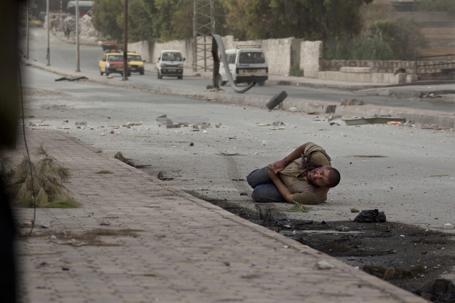 A wounded Syrian civilian lies in the street with a shot to his stomach as he tries to escape the line of fire after he was targeted by a Syrian army sniper while walking near the frontline in the Bustan al-Qasr neighborhood of Aleppo, Syria, Oct. 20, 2012. (Narciso Contreras, Associated Press - October 20, 2012)