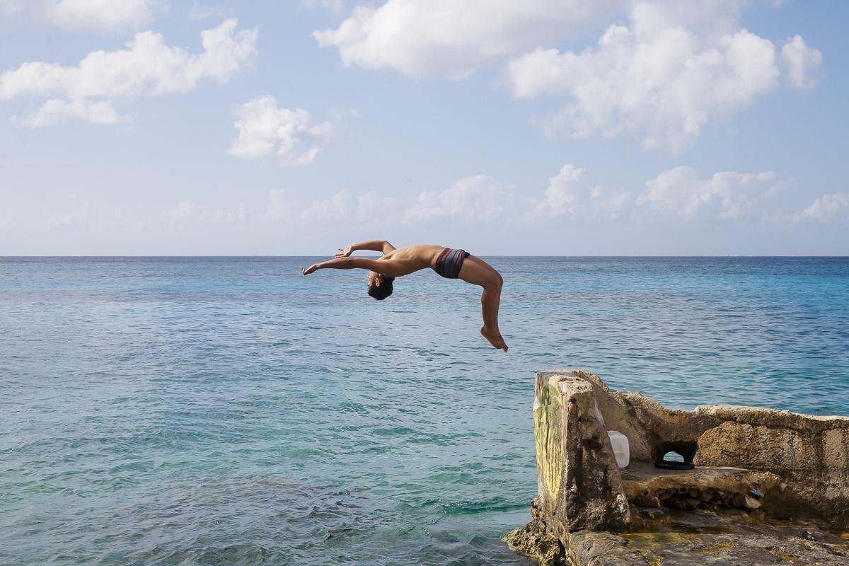 A guy doing a back flip in Cozumel