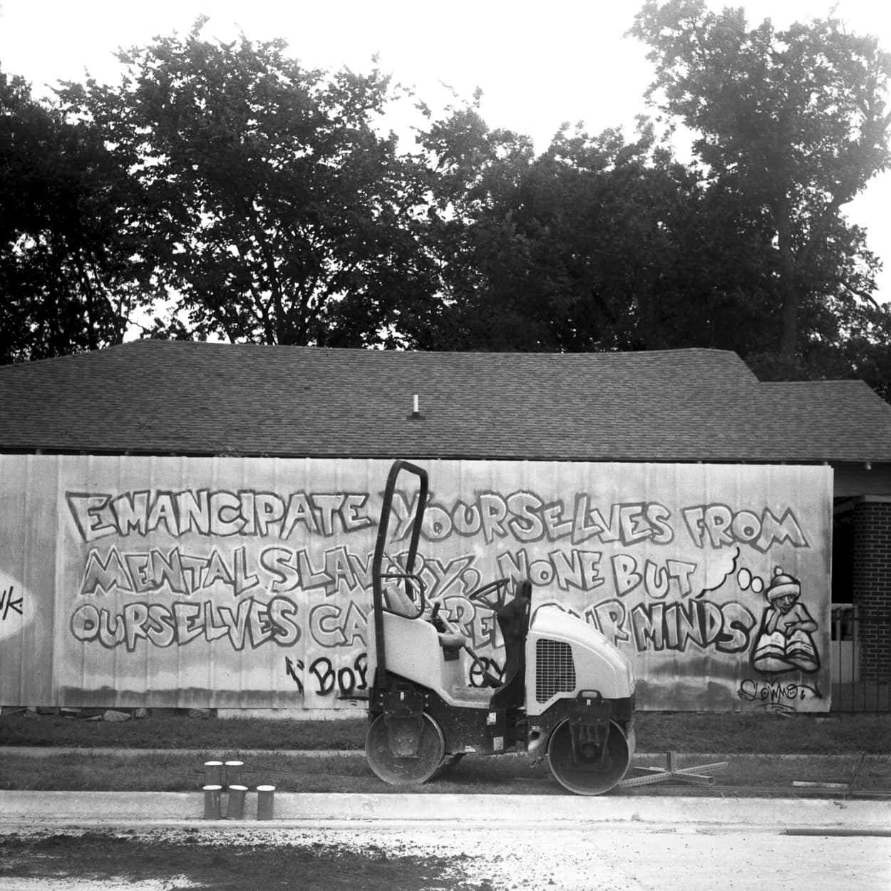 A road roller in front of graffiti quoting by Bob Marley