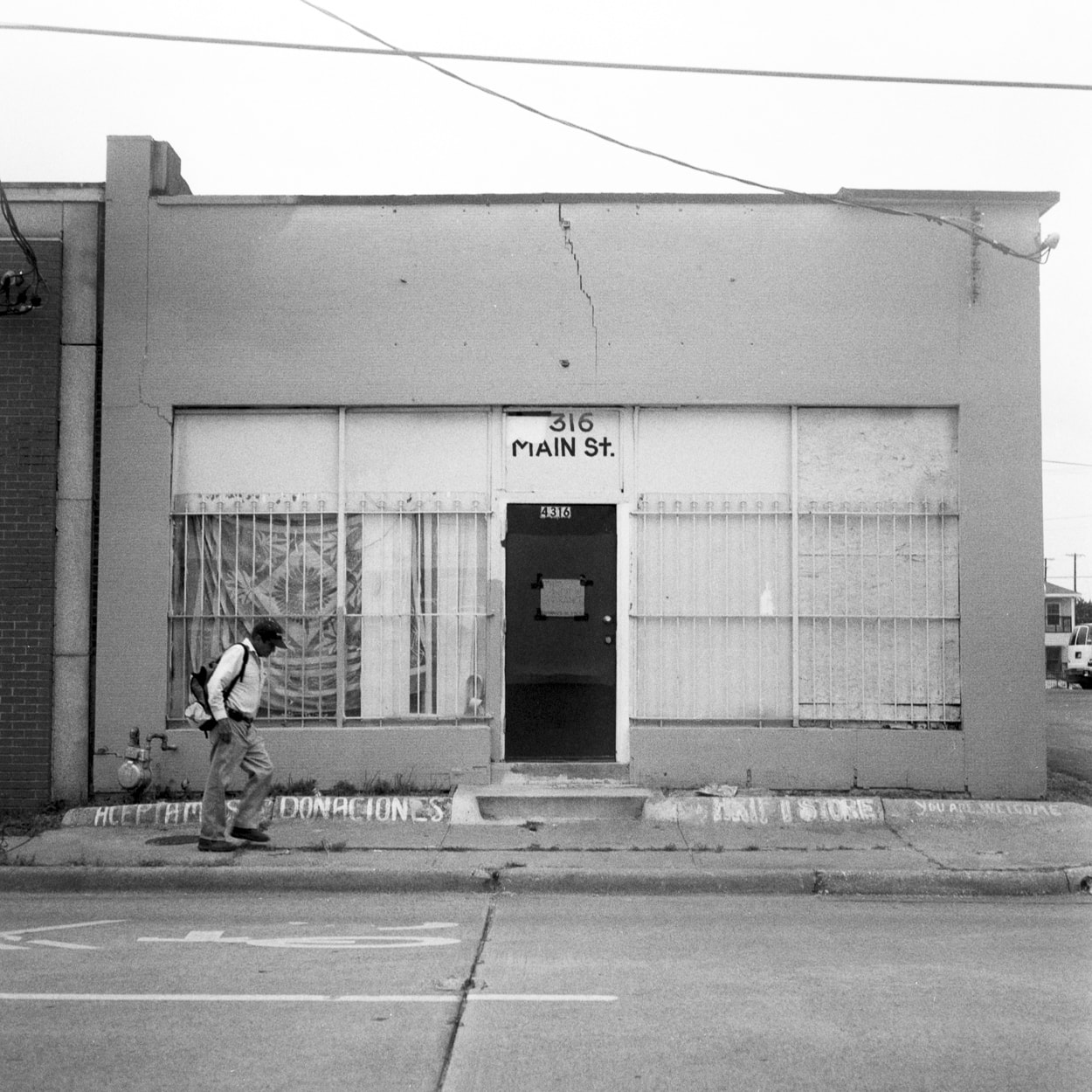 A man walking in front of an old store front
