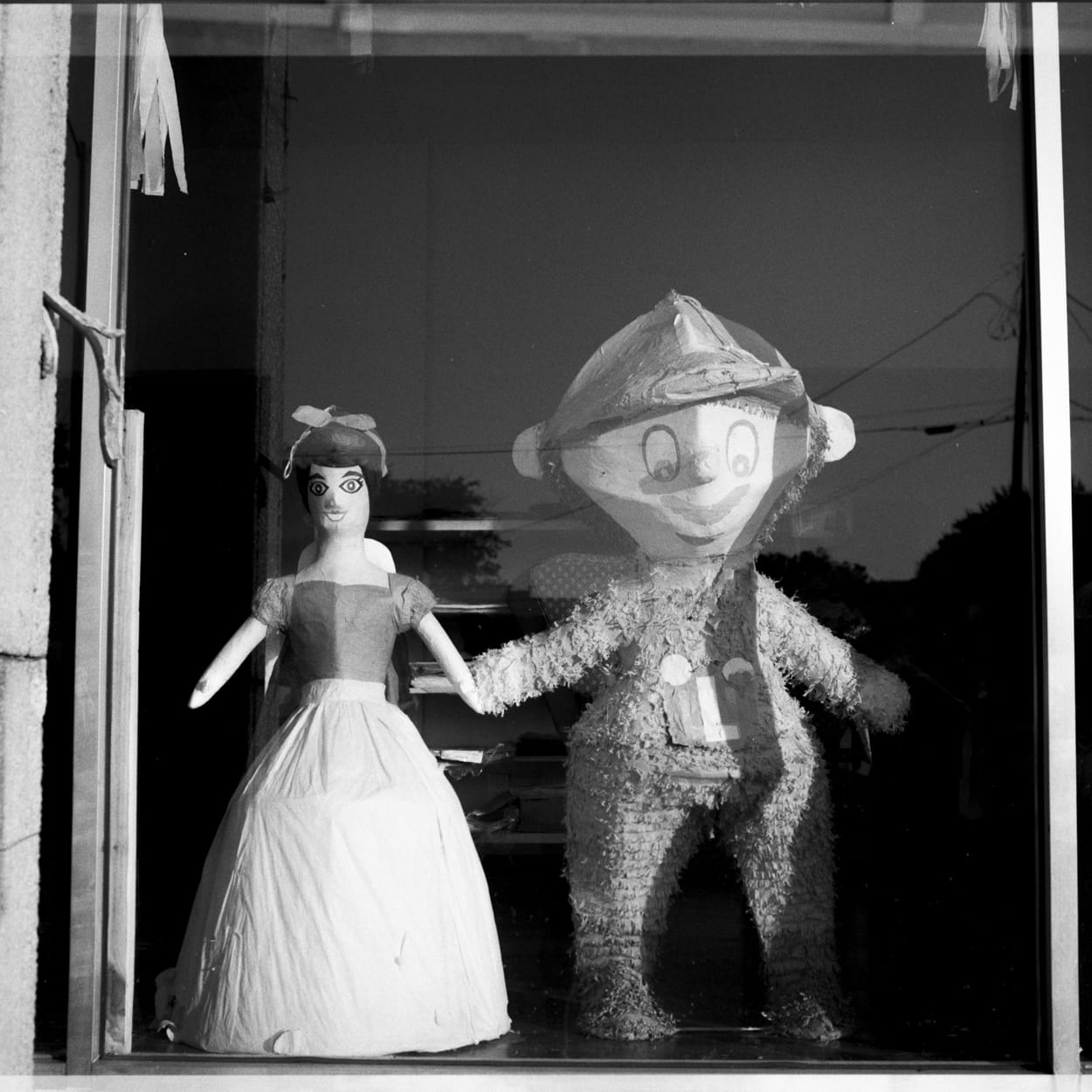 Snow White and Mario piñatas holding hands like two lovers in a window display