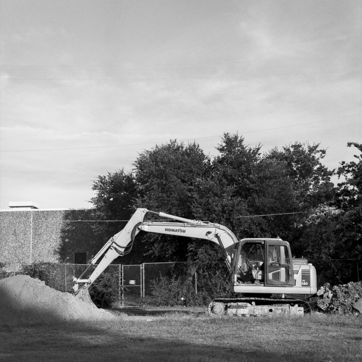 An excavator clearing a plot of land
