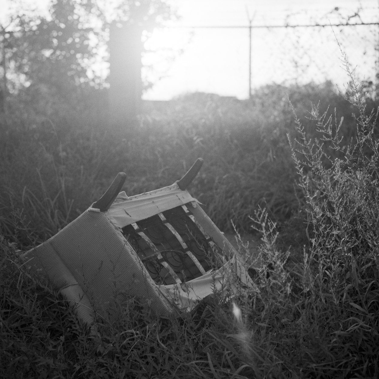 A discard chair in grass on the side of the road