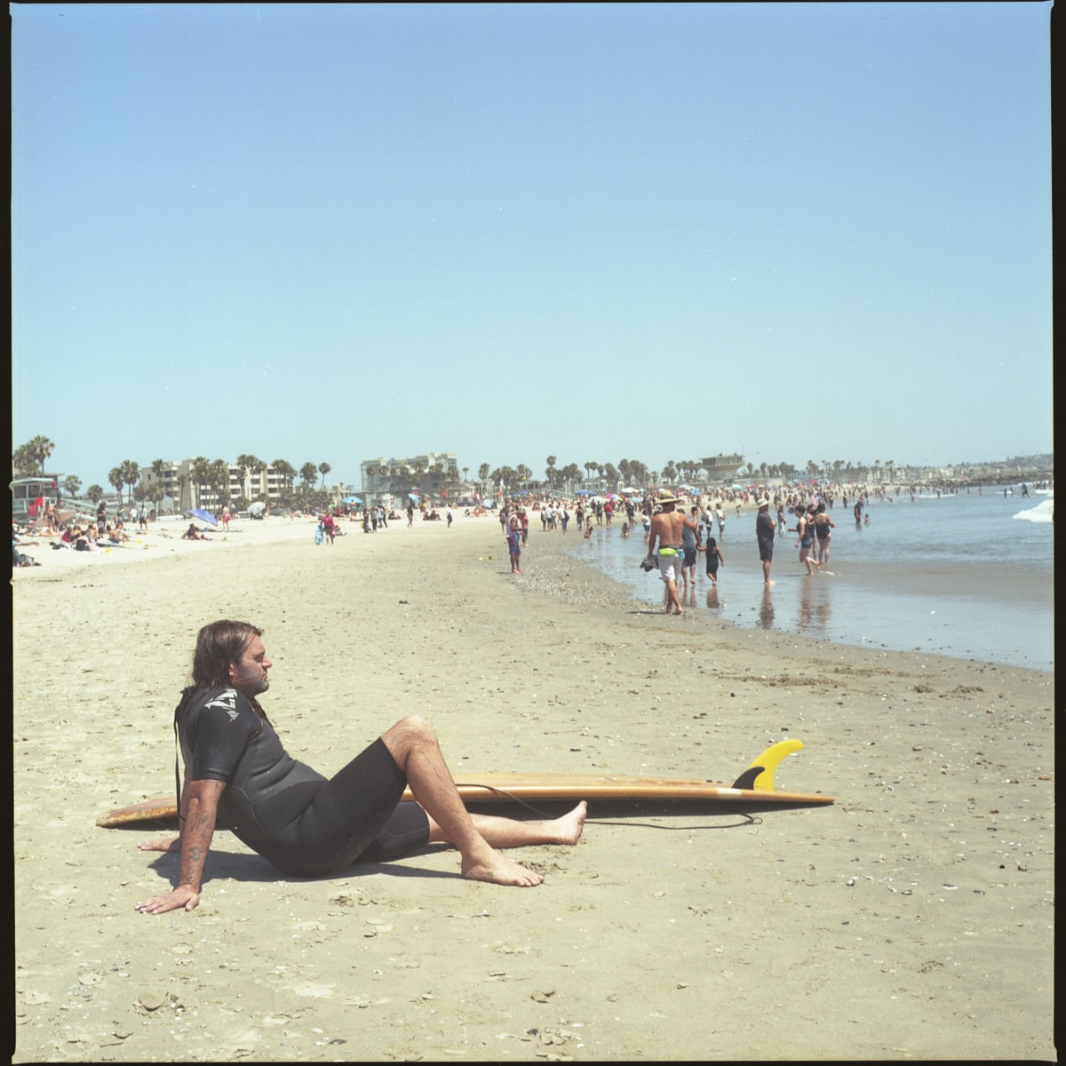 A surfer relaxing on the beach, California