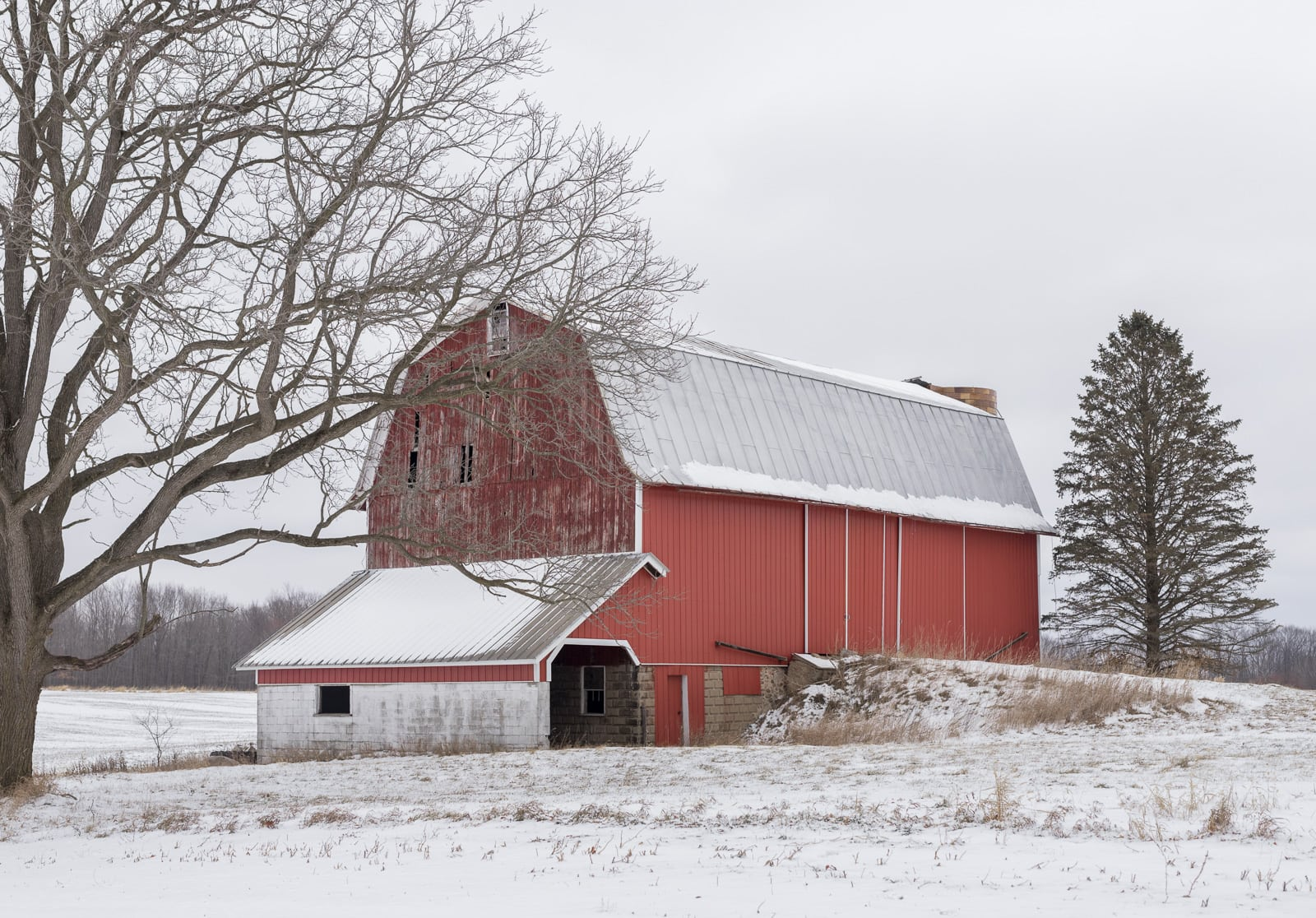 Old Red Dutch barn covered with snow