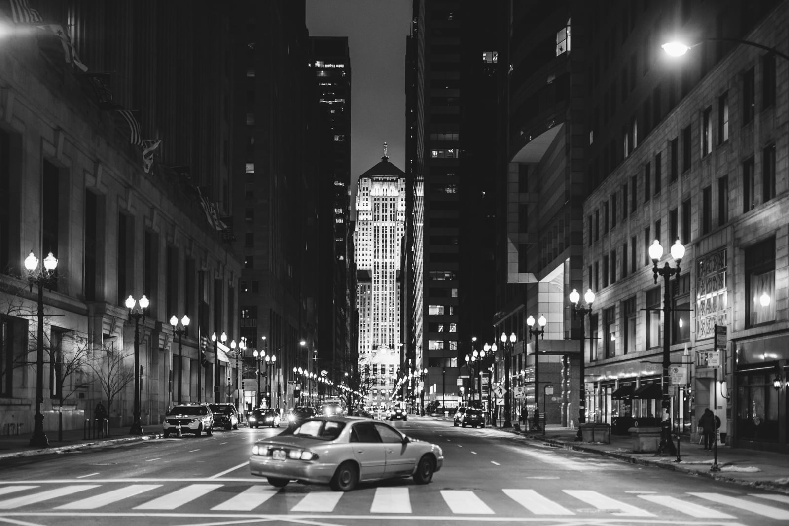 An old car turning in an empty streets of Chicago