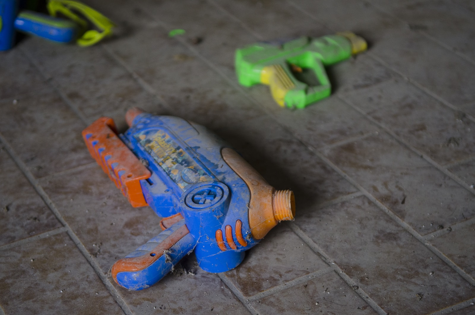 A dusty toy gun on the ground in an abandoned house