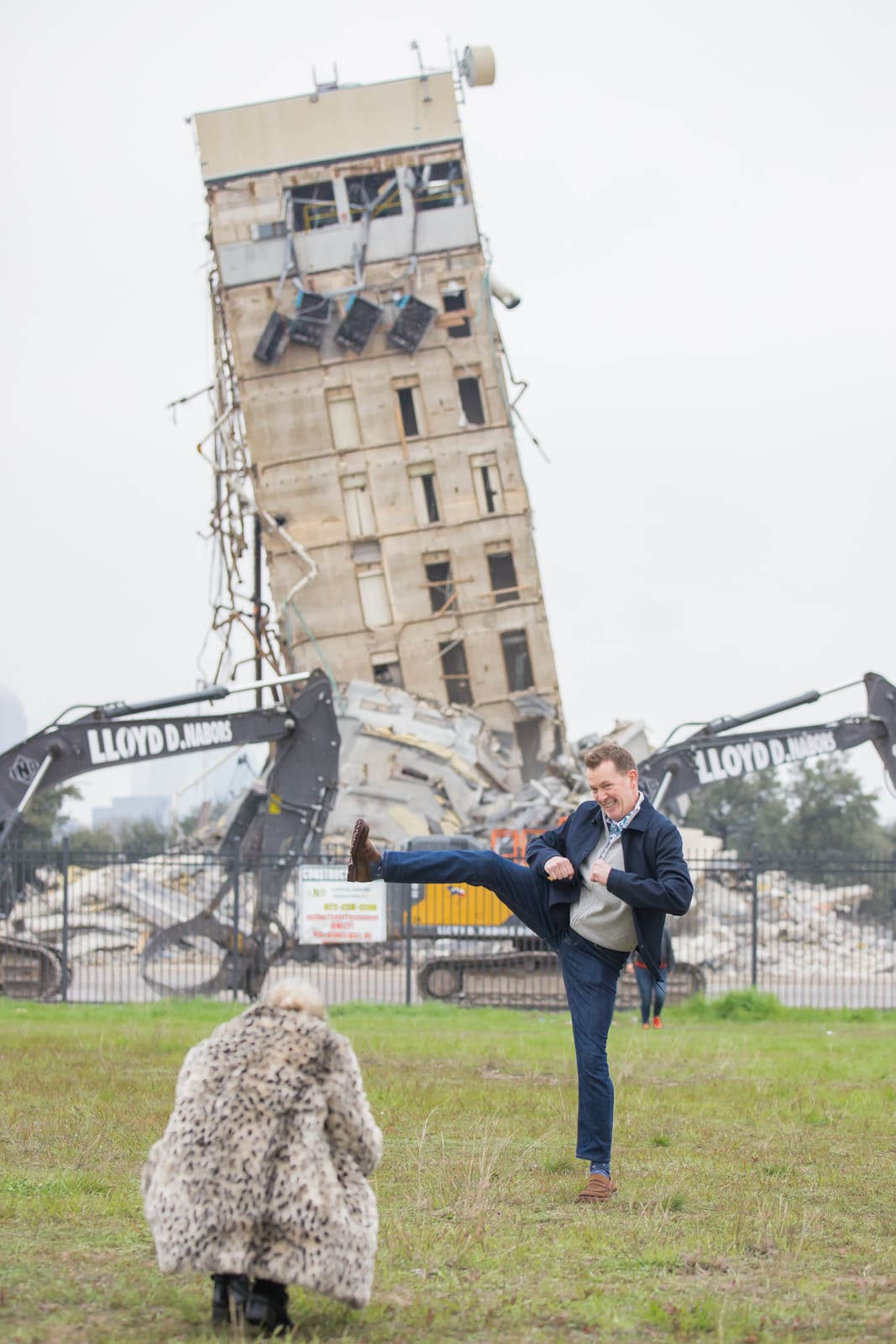 """A man posting with the """"Leaning Tower of Dallas."""" 2020 Best Photos."""