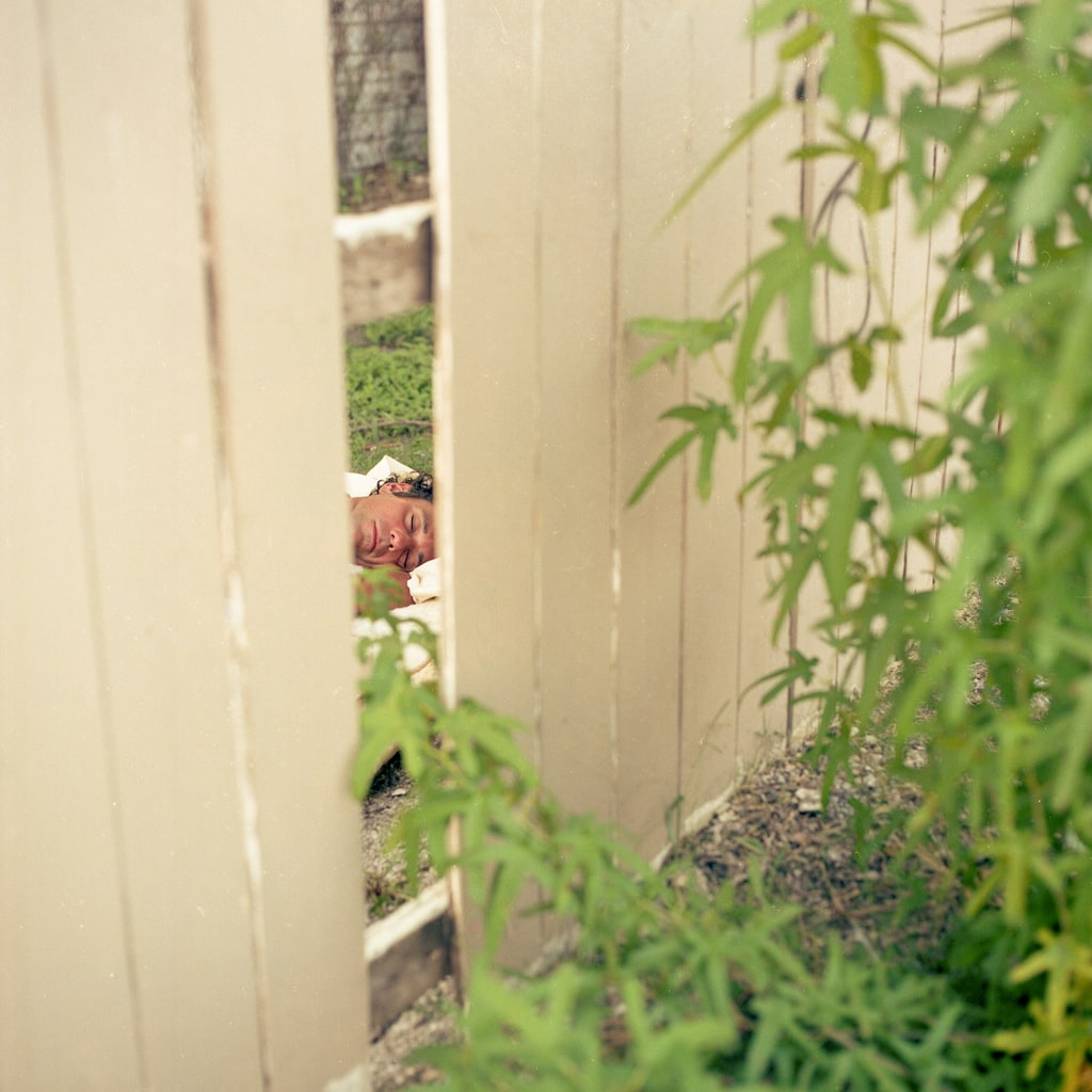 A man sleeping seen through a fence with a missing board in Dallas, Texas. Best Photos of 2020