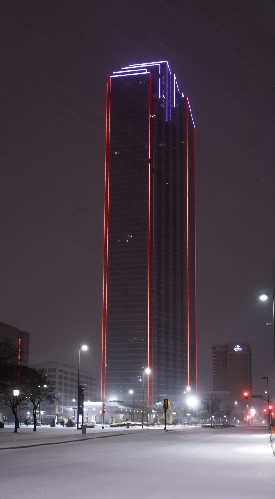 Bank of America Plaza with red lights at night on a snowy evening