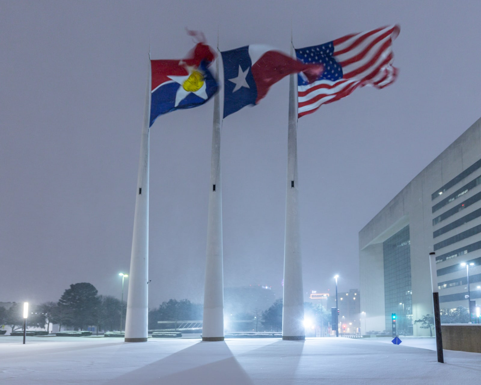 City of Dallas flag, Texas flag, and United States Flag blowing a snowstorm