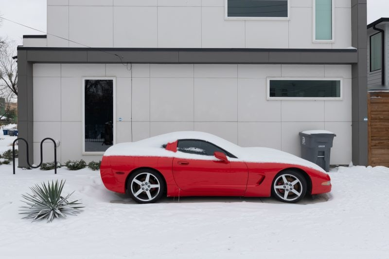 A red corvette partially buried with snow