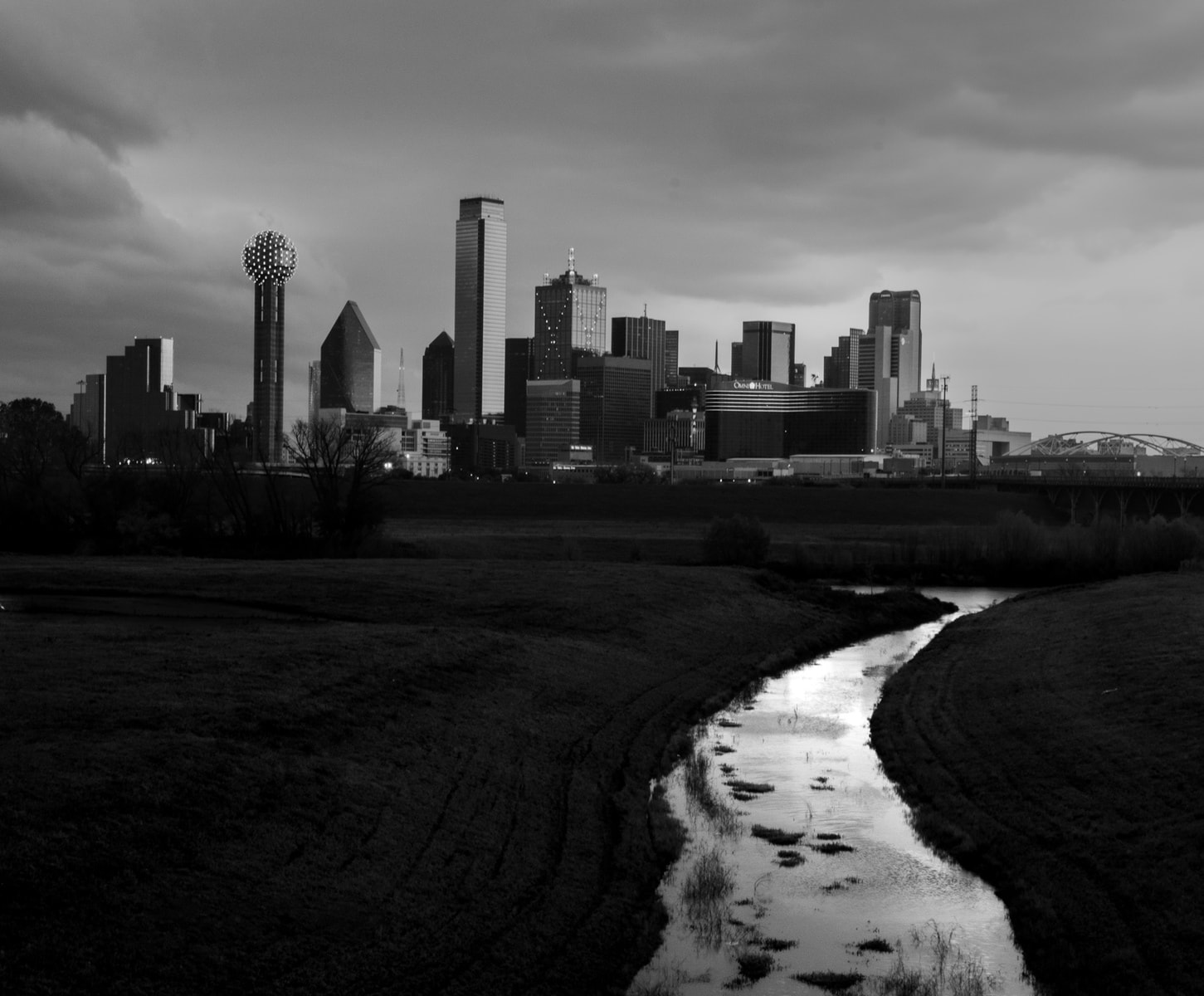 A black and white photo of The Dallas skyline with the trinity river
