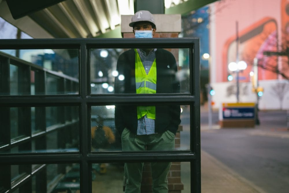 A city worker standing behind a glass wall at a bus stop
