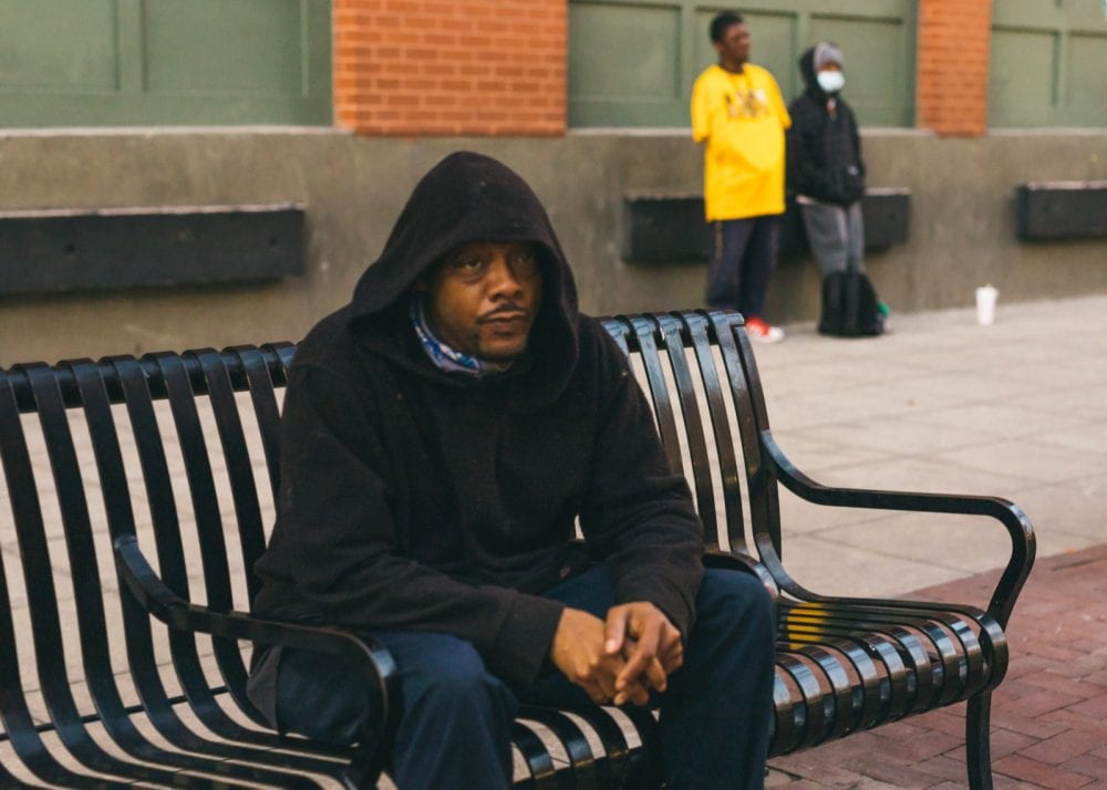 Man sitting on bench at a train station in Dallas