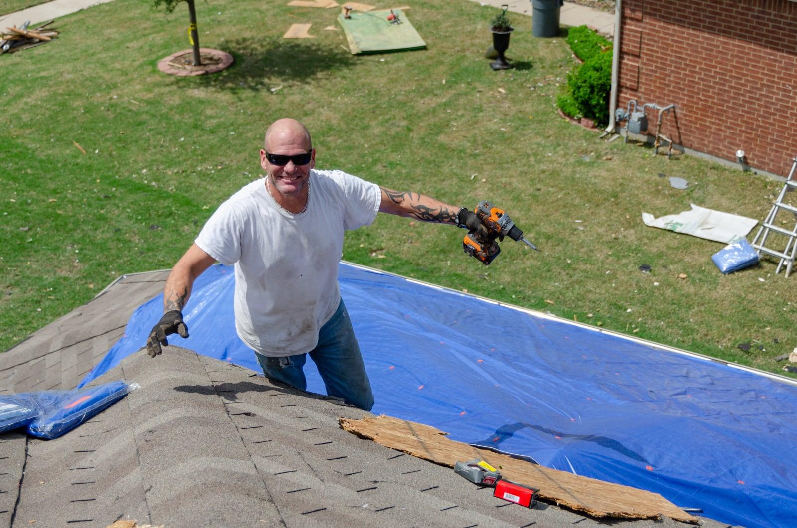 A man helping repair his friend's roof