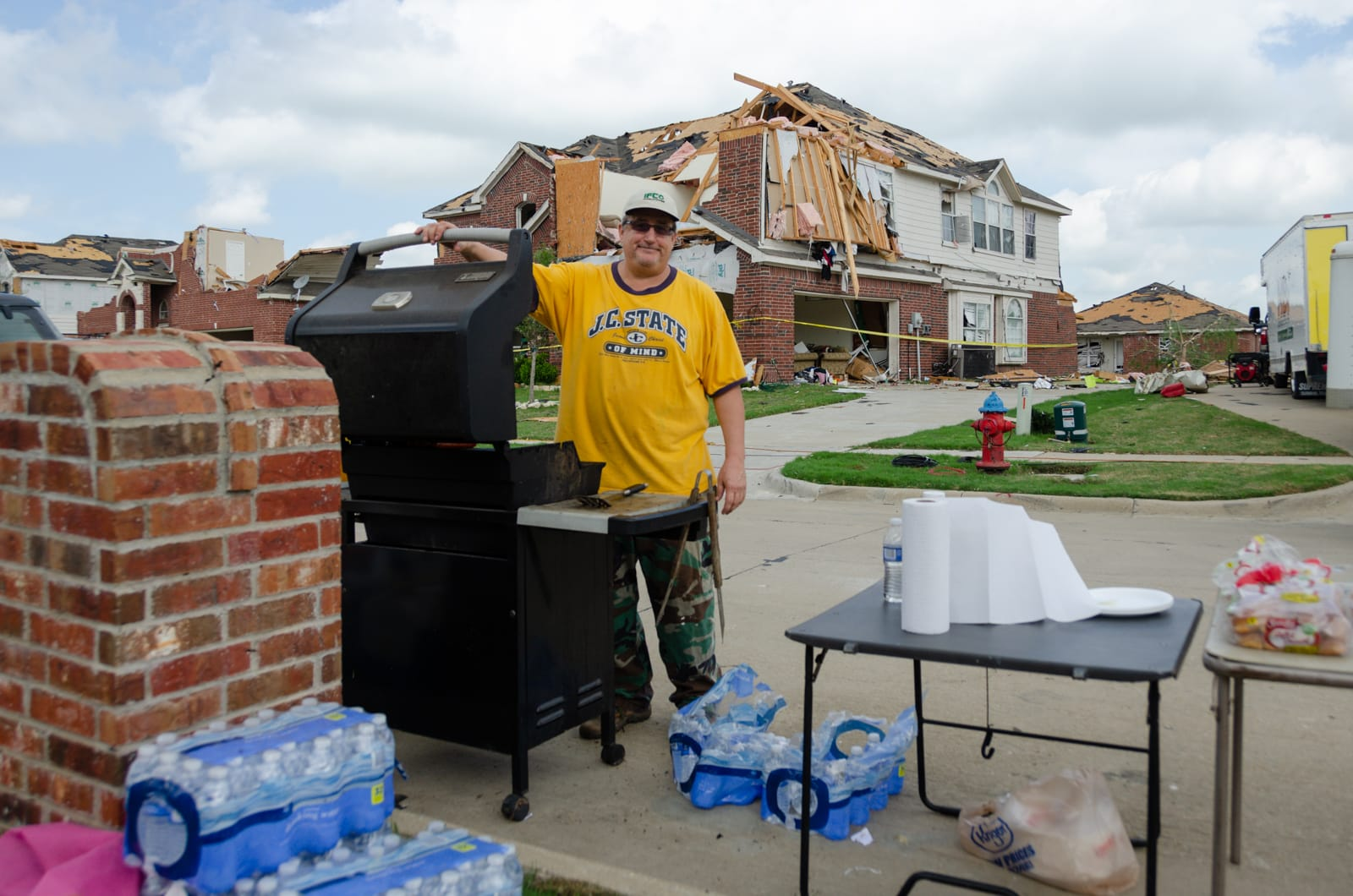 Steve grilling food for people who are cleaning up after their homes were hit by a tornado