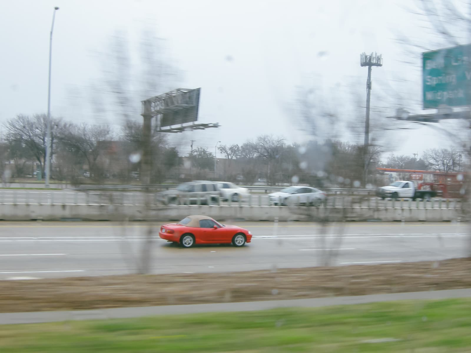 A red car driving on highway 75