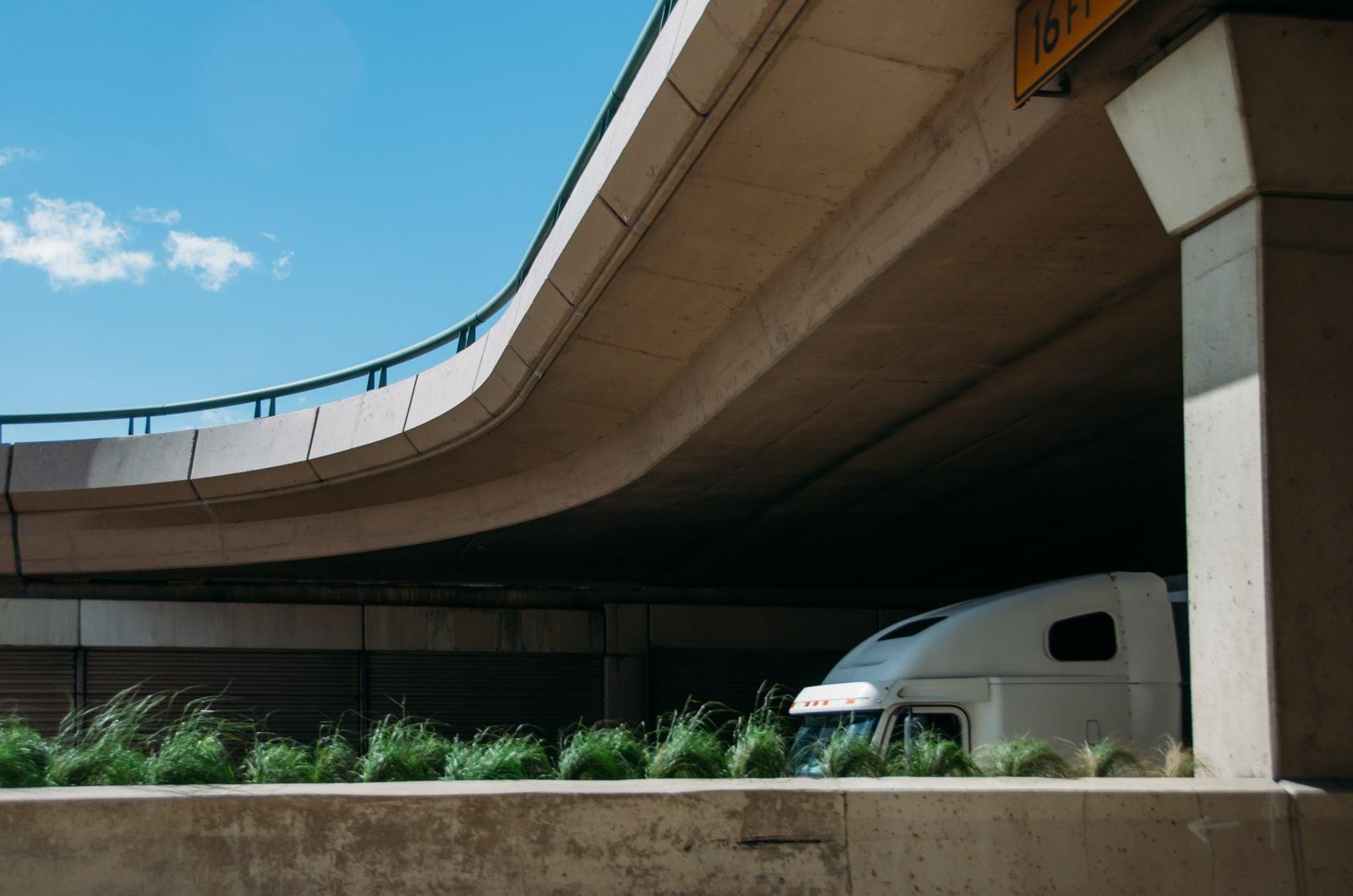 A semi going under a bridge on highway 75