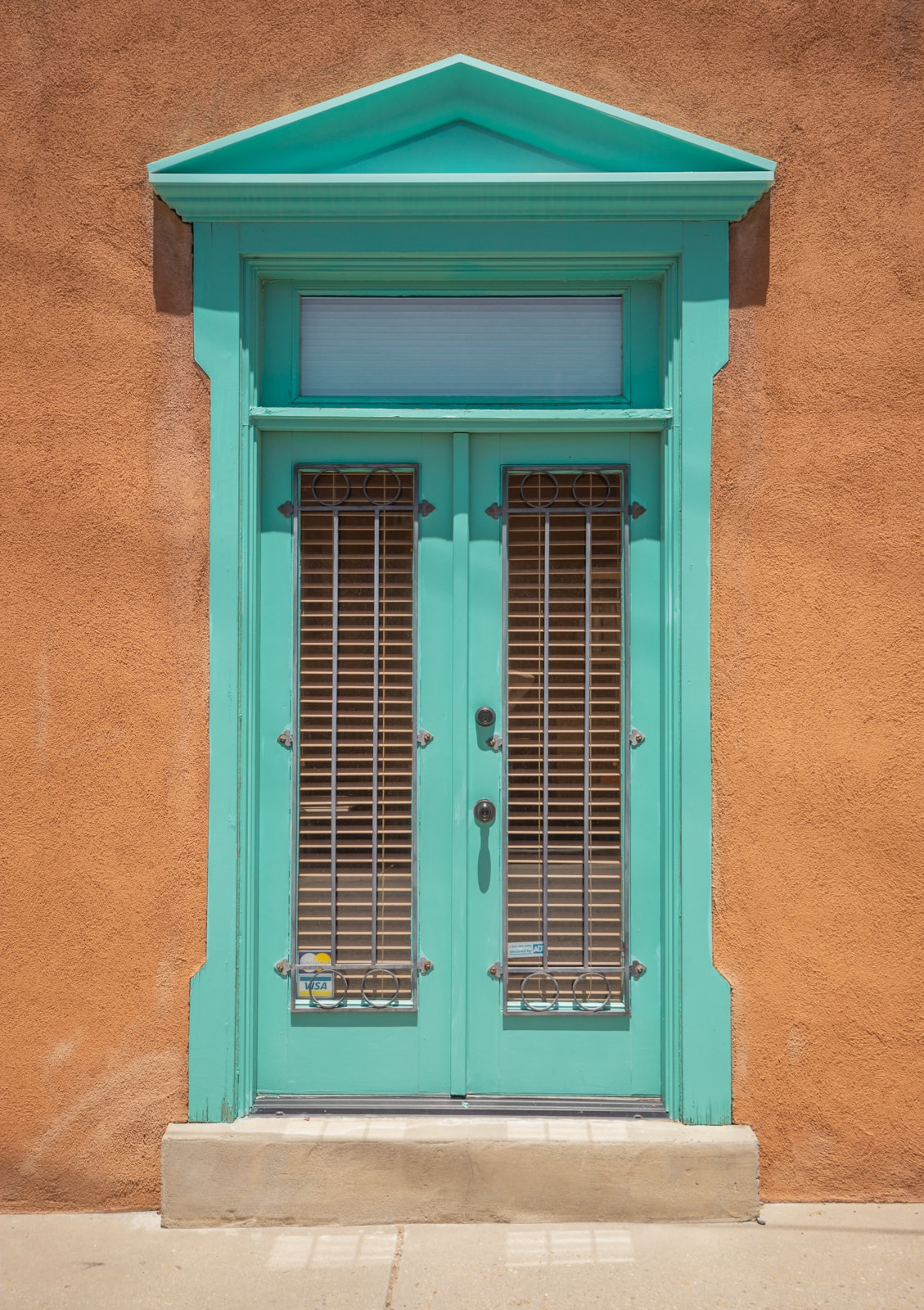 A turquoise window frame in an adobe style building