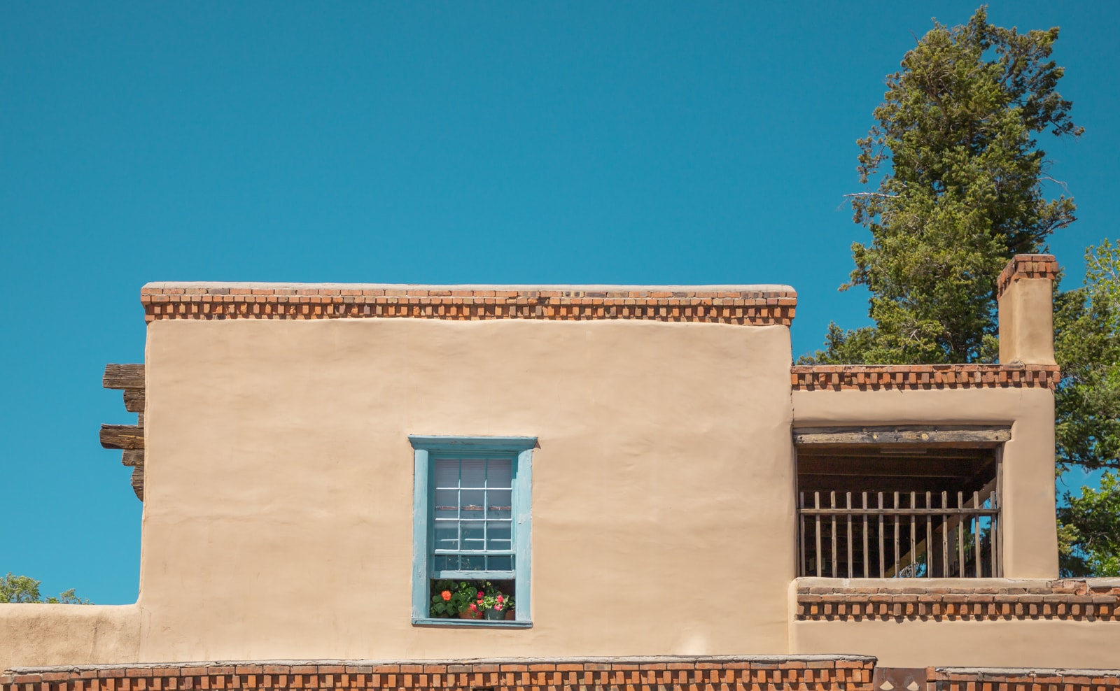 Flowers in the window of a Pueblo Revival style home
