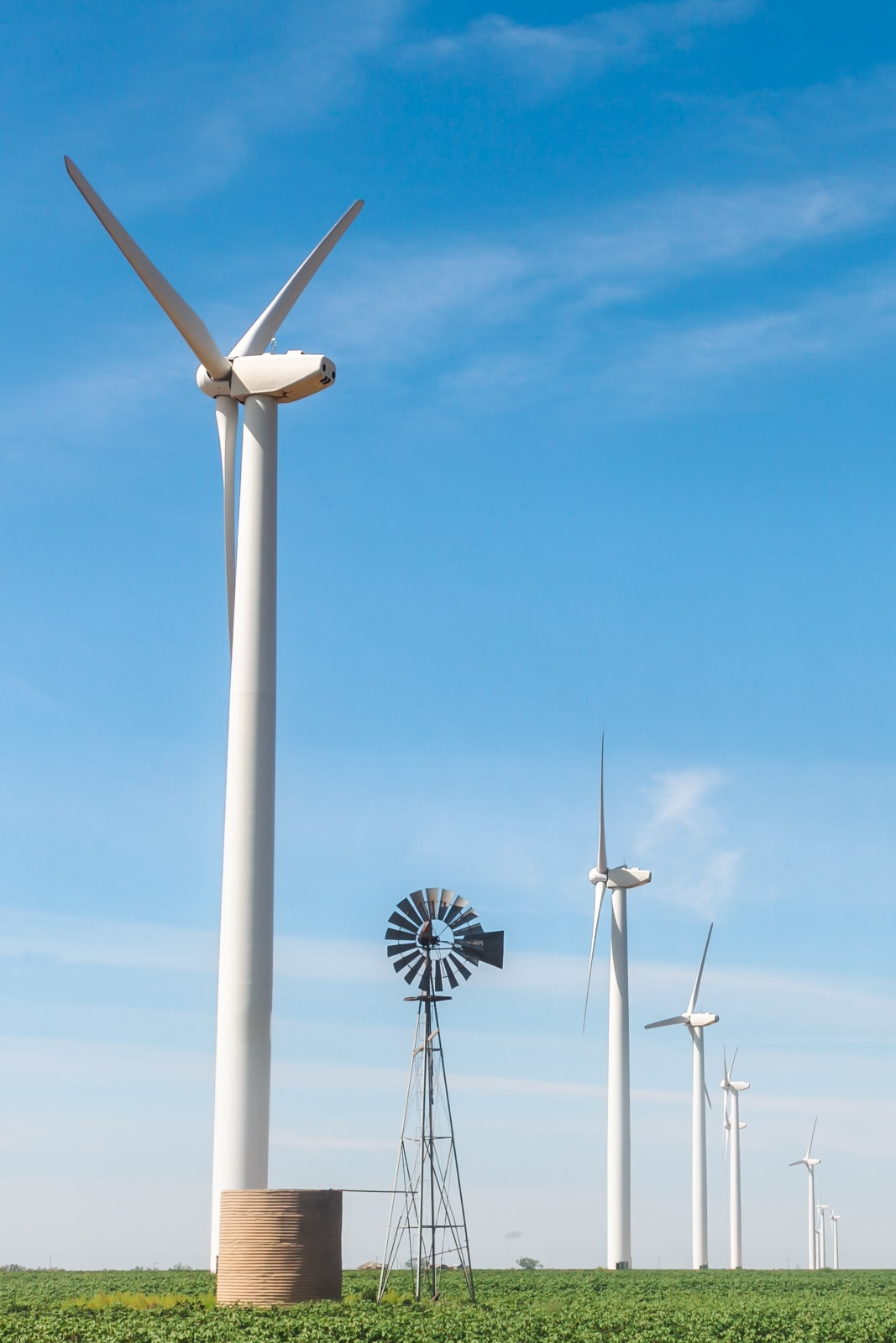 An old wind mill with new wind mills