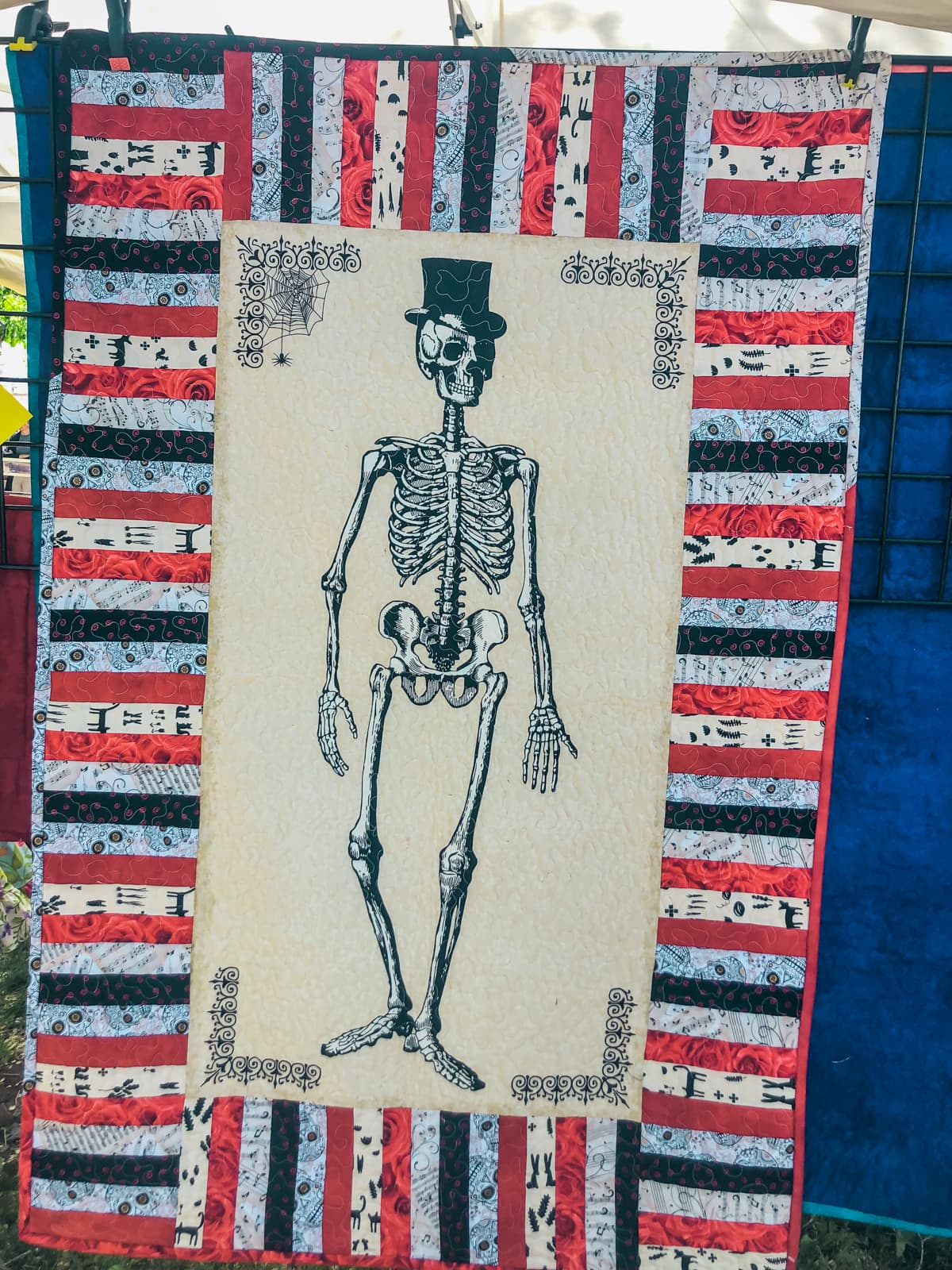 A blanket with a skeleton in a top hat on it