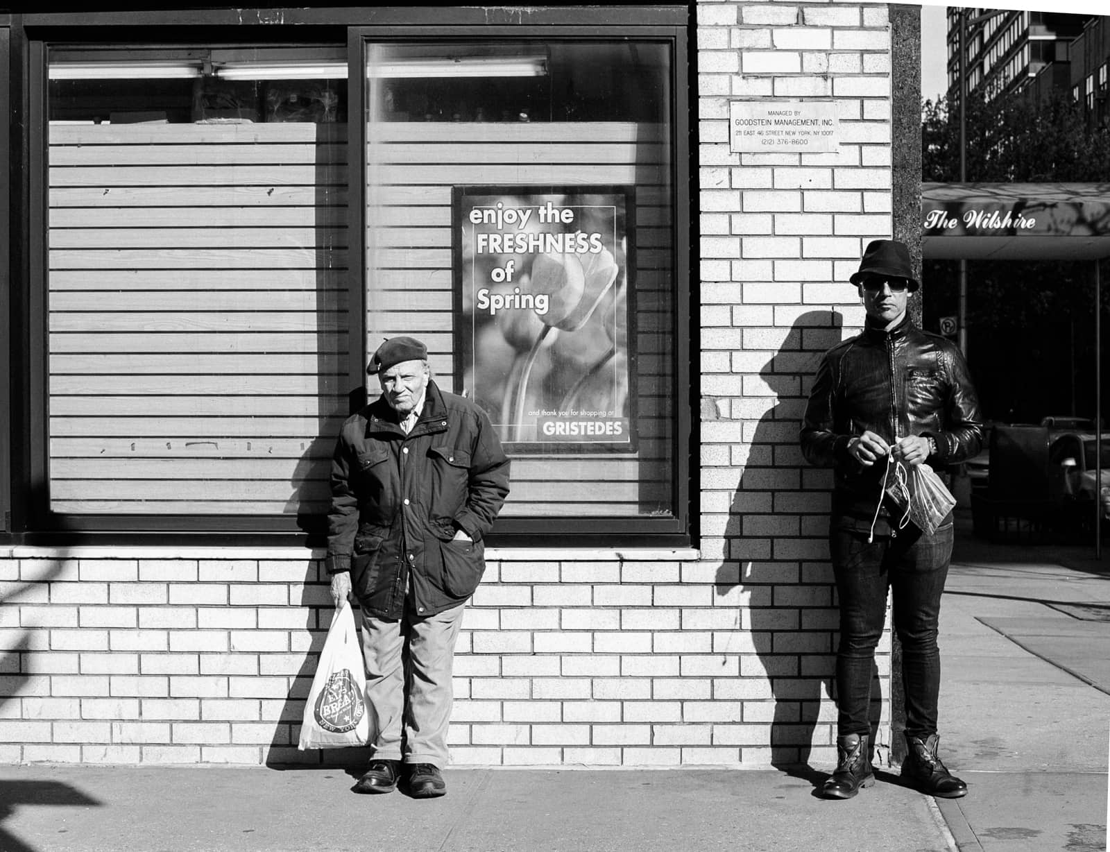 An older man and a young main waiting for the bus