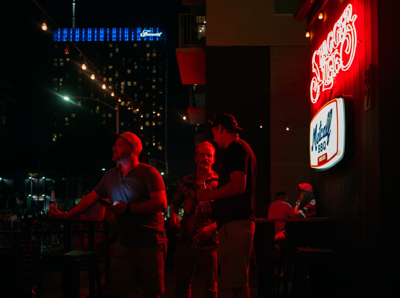Three men talking below a red neon sign at Stagger Lee bar on Rainey Street